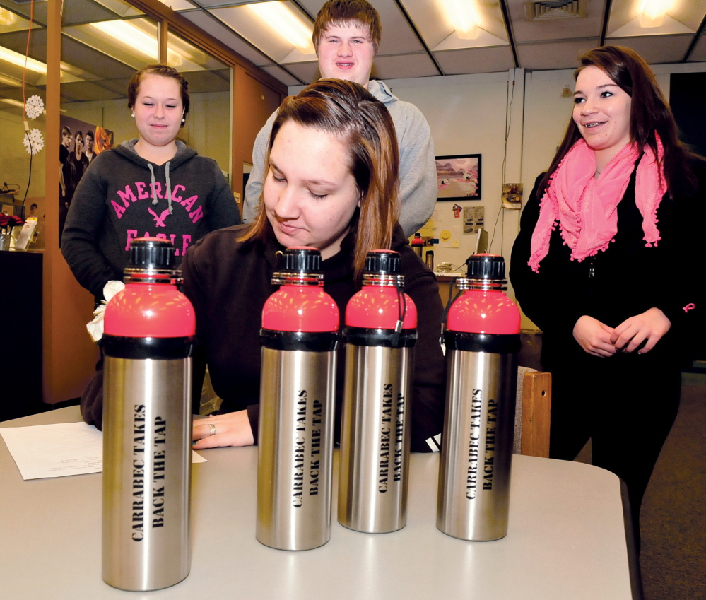 REDUCE AND REUSE: Carrabec High School student Emily Poulin signs a pledge Tuesday to reduce plastic waste by using reusable bottles, foreground. Waiting to sign the pledge, from left, are Taylor Stewart, Jacob Turner and Emily Witham.