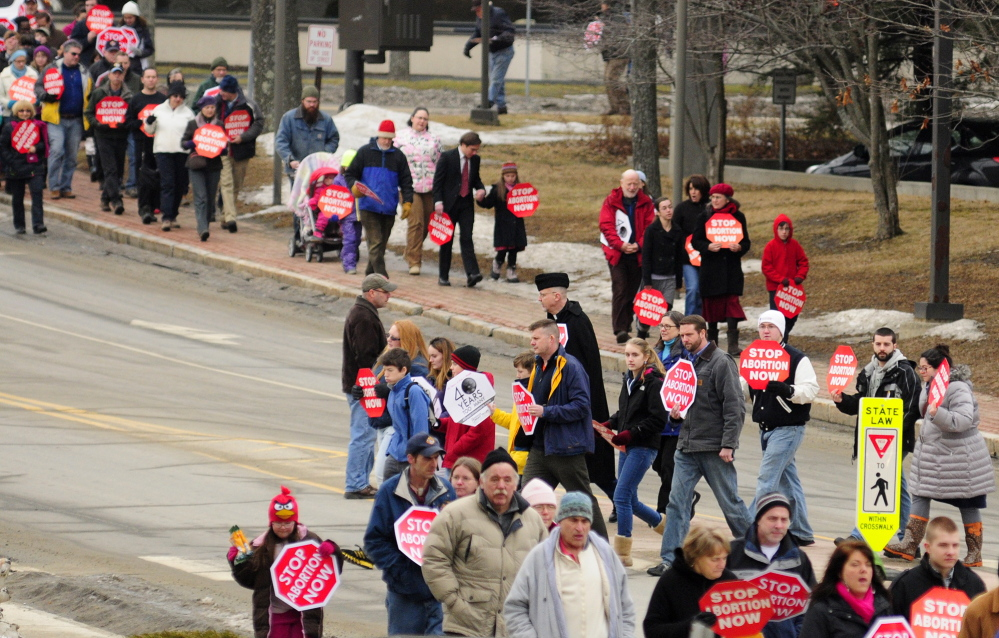 Signs of the times: Anti-abortion protesters cross Capitol Street on Saturday on their way to take part in the Hands Around the Capitol Memorial at the State House, in Augusta. The group held hands around the State House and rang a bell there 41 times during the event held to mark the 41st anniversary of the Supreme Court's Roe v. Wade decision.