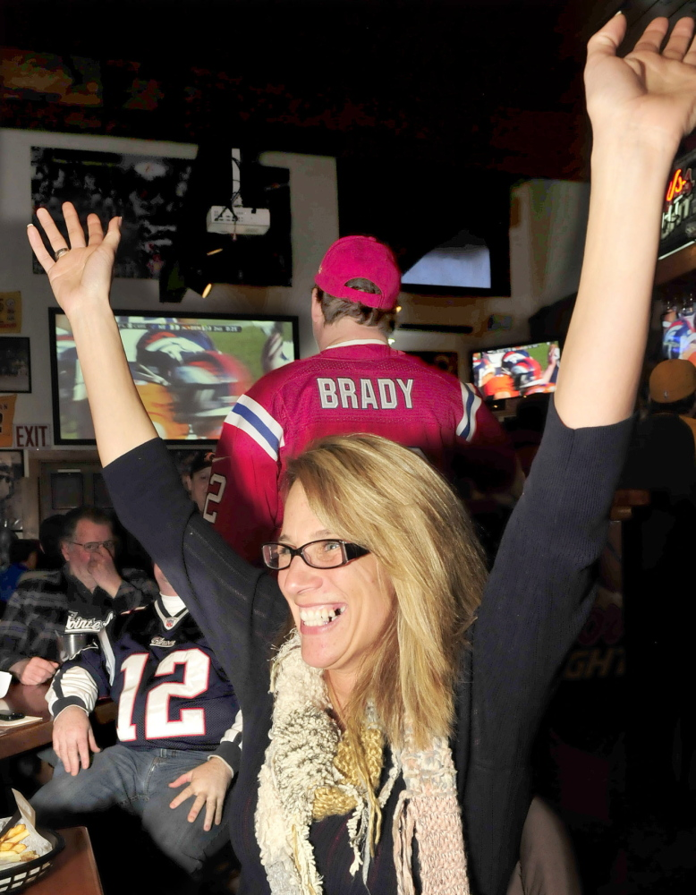 Staff photo by David Leaming MINORITY: Denver Broncos fan Debbie Patterson reacts to a field goal by her team while surrounded by New England Patriots fans during AFC championship game at the Pointe Afta in Winslow on Sunday, Jan. 19, 2014.