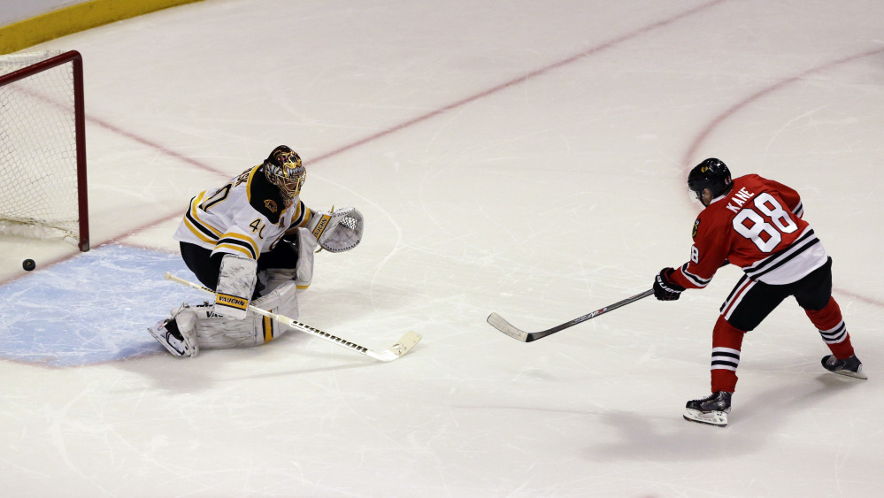 Chicago Blackhawks' Patrick Kane, right, scores against Boston Bruins goalie Tuukka Rask during the shootout of an NHL hockey game in Chicago, Sunday, Jan. 19, 2014. The Blackhawks won 3-2. (AP Photo/Nam Y. Huh)