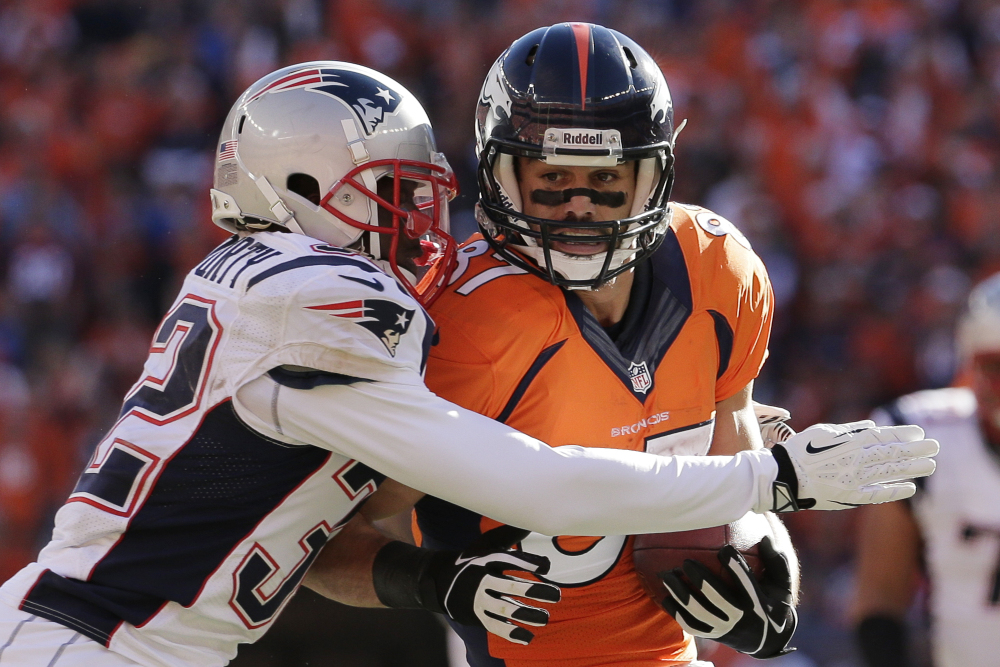 Patriots free safety Devin McCourty wraps up Denver wide receiver Eric Decker in the first half Sunday in the AFC championship game at Denver.