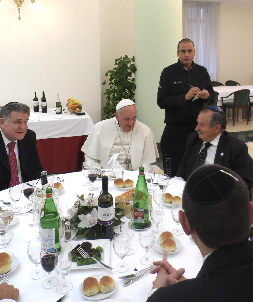 Ba' Ghetto restaurant co-owner Amit Dabush, top right, takes notes as Pope Francis, center, and Rabbi Abraham Skorka, left, have lunch at the Vatican on Thursday.