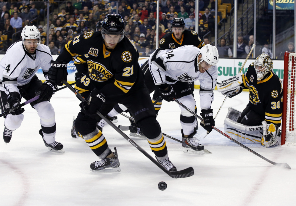 Bruins left wing Loui Eriksson (21) controls the puck against Los Angeles Kings right wing Justin Williams (14) and left wing Dwight King (74) as Bruins goalie Chad Johnson (30) protects the net during the first period in Boston on Monday.