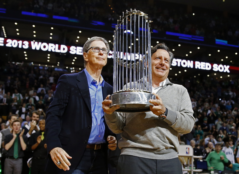 Boston Red Sox owner John Henry, left, and chairman Tom Werner hold the 2013 World Series trophy before an NBA game between the Boston Celtics and the Milwaukee Bucks in Boston on Nov. 1.