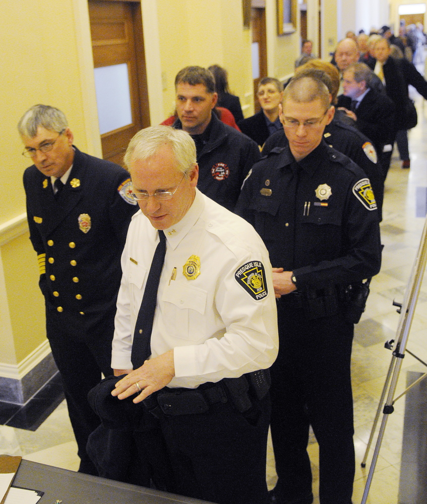 Presque Isle Police Chief Matthew Irwin is flanked by firefighters from his community Wednesday as he signs up to testify at the Legislature's Appropriations Committee in Augusta on municipal aid from the state. Police officers, firefighters and town officials lined up to testify on the bill that would avoid a $40 million cut in municipal revenue sharing by eliminating tax breaks and trimming economic development programs. The bill faces an uphill battle but could impact property taxpayers if revenue sharing is cut.