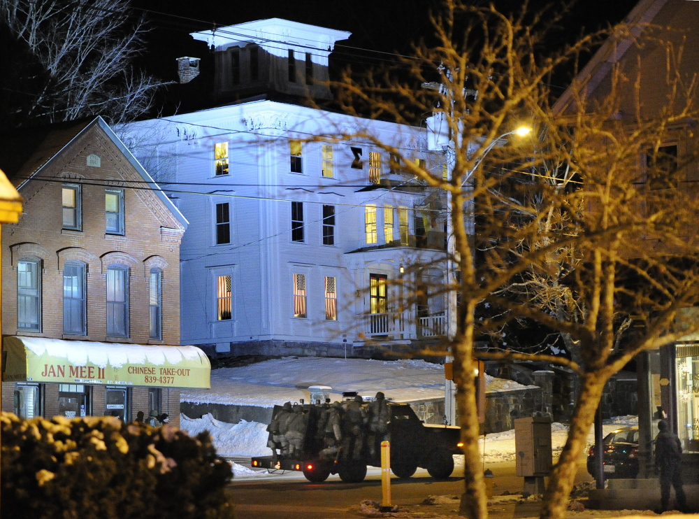 An armored vehicle carrying police tactical team members shines a bright light on the University of Southern Maine fraternity building where an armed student was involved in a standoff Wednesday night in Gorham.