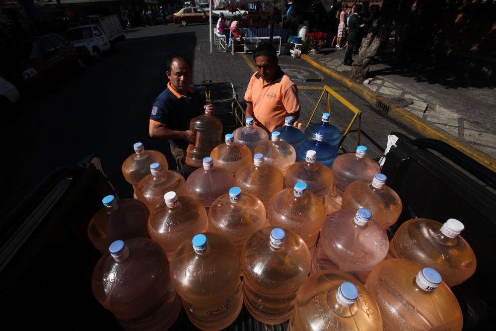 A vendor prepares to fill his bicycle cart with 18-liter jugs of bottled water to sell to owners of street food stalls in Mexico City.
