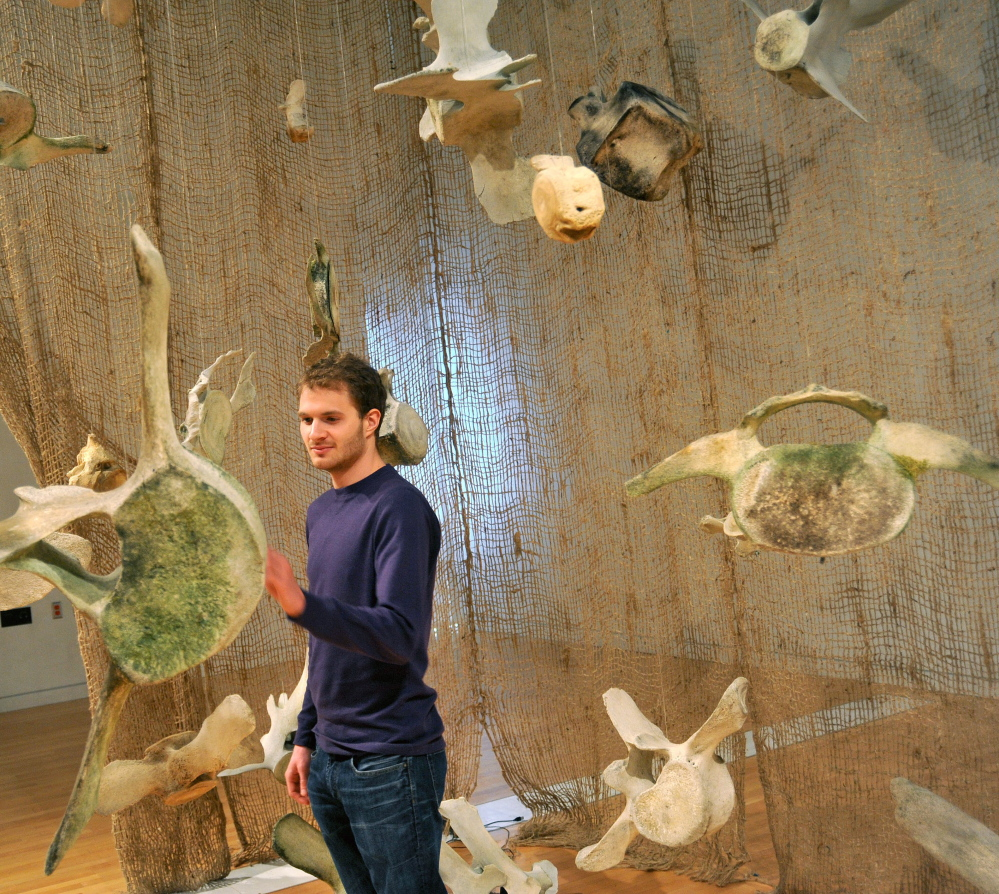 UP CLOSE: Josh Rose, 22, takes a closer look of a whale bone Friday in the Flex Space at the Emery Community Arts Center at the University of Maine at Farmington. The exhibit includes the bones of whales native to the Gulf of Maine. Visitors are encouraged to touch and move pieces in the hands-on exhibit.