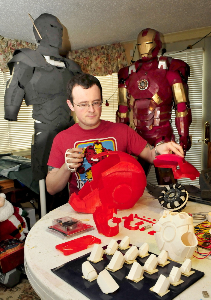 NEW AGE SCIENCE: Tom Lemieux assembles helmet pieces of his new Iron Man character outfit that were made from a 3-D printer and will replace the original outfit, at right.