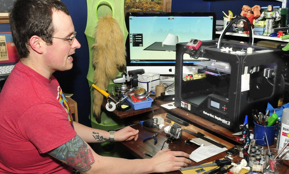 HIGH TECH: Tom Lemieux monitors a 3-D printer that is making plastic parts for an Iron Man outfit at his home in Oakland.