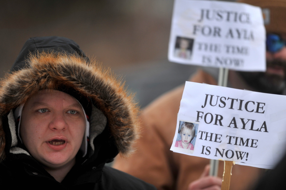 awareness: Ann Carrillo, 37, of Waterville, holds a sign Saturday during a demonstration to raise awareness about the open missing-toddler case at the Waterville police station.