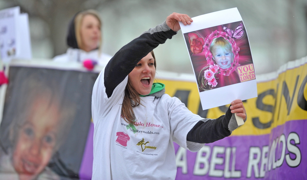 remember: Trista Reynolds, mother of missing toddler Ayla Reynolds, holds a picture of her daughter at the Colby Circle and College Avenue intersection in Waterville on Saturday.
