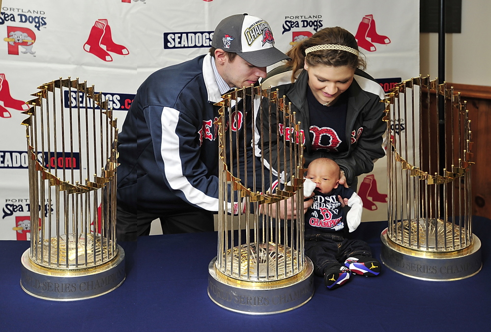 Devan Knight, left, and Ashli Canabush of Lisbon Falls, sit their 2-week-old baby, Brayden, among the three World Series trophies on display at Hadlock Field on Saturday. Devan Knight was a group sales employee for the Sea Dogs in the past.