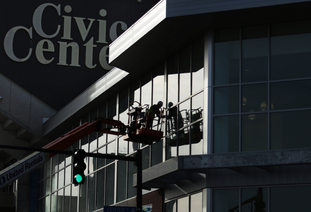 Jonni Merrill of New Hampshire Glass works on a curtain wall on the exterior of the newly renovated Cumberland County Civic Center on Spring Street in downtown Portland recently.