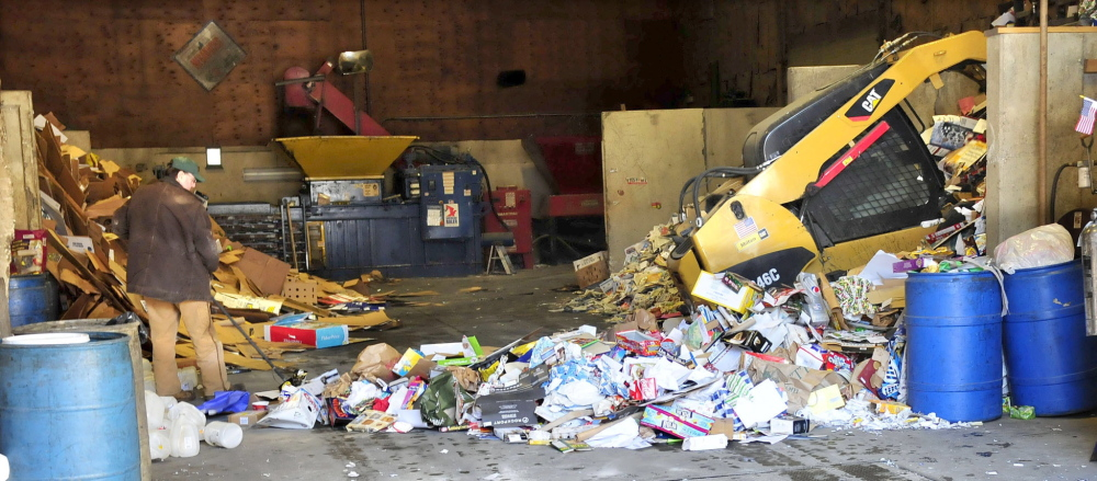 PACKING: Workers use machinery to pile paper inside the Sandy River Recycling Center in Farmington on Thursday. The center will close by June 30.