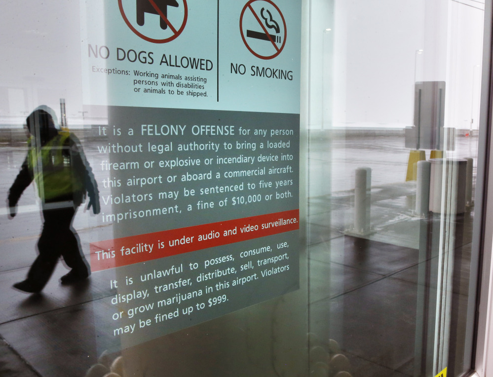 A security officer walks near a notice prohibiting marijuana possession at Denver International Airport.