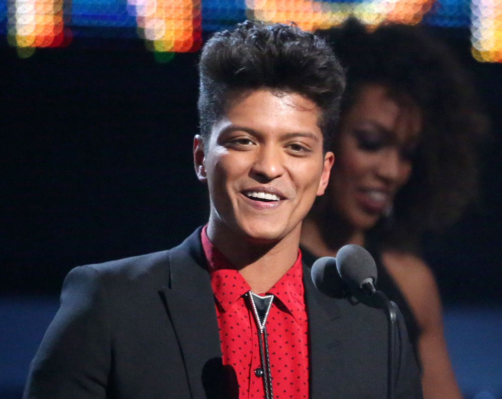 """Bruno Mars accepts the award for best pop vocal album for """"Unorthodox Jukebox"""" at the Grammy Awards in Los Angeles on Sunday. Mars will perform at the Super Bowl halftime show Sunday."""