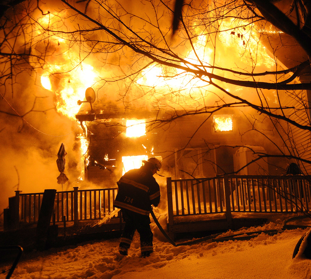 BURNING BRIGHT: A firefighter attempts to extinguish a blaze Friday that destroyed a home on Northern Avenue in Farmingdale. No injuries were reported, according to firefighters.