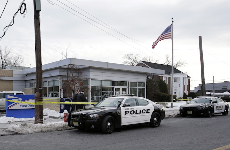 Police officers stand guard outside the closed post office in Wood-Ridge, N.J., Friday, Jan. 31, 2014. The FBI says a powder mailed to several locations in New York and New Jersey, including at least five hotels near the site of Sunday's Super Bowl appears not to be dangerous.