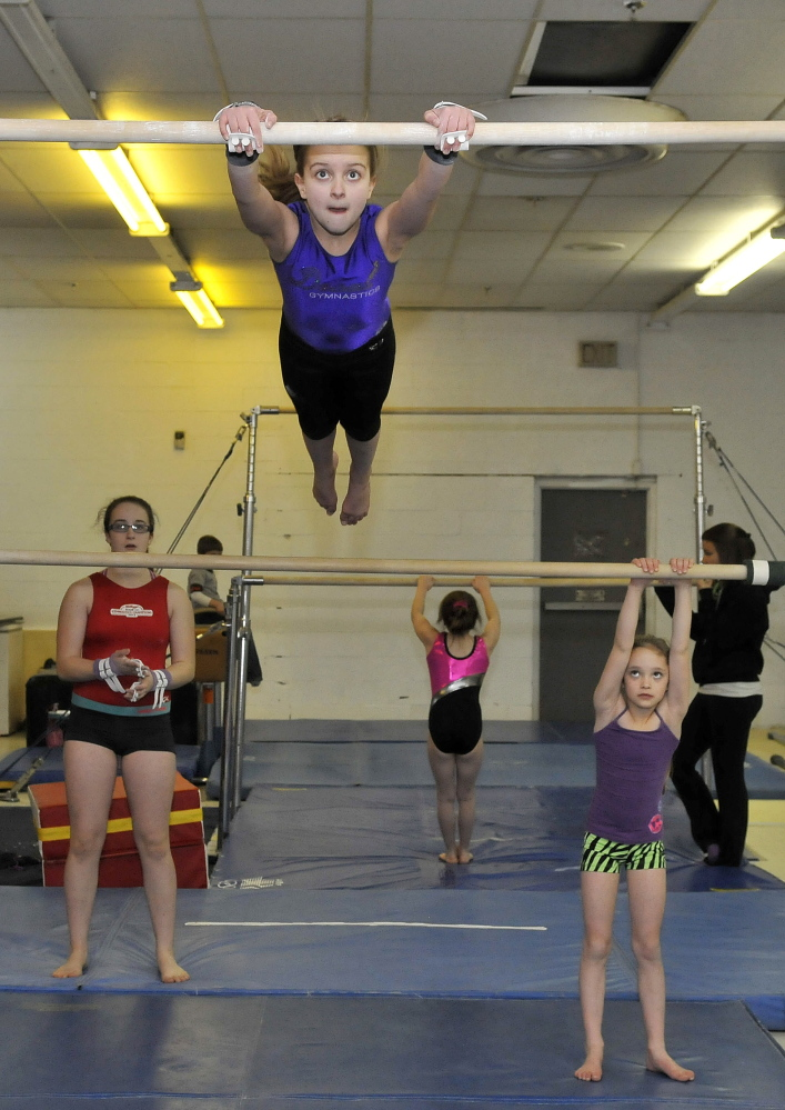 Raising the bar: Rachel Hanson, 10, top bar, practices the uneven bars at Decal Gymnastics in Farmington on Saturday. Decal re-opened today after closing because of flooding.