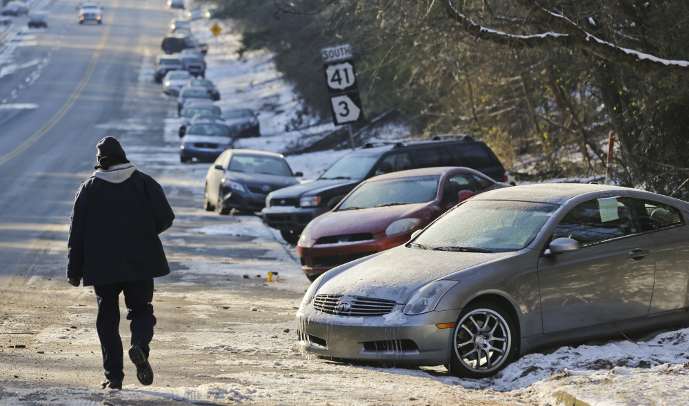 Abandoned cars sit idle along Northside Parkway in Atlanta on Thursday. State agencies including Georgia State Patrol, National Guard and Georgia Department of Transportation (GDOT) HEROs started using four-wheel-drive vehicles to transport motorists back to their vehicles from two metro Atlanta locations.