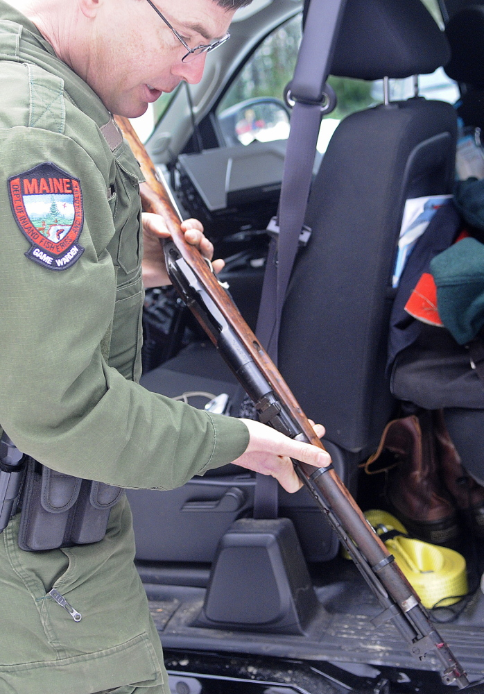 Firearm confiscated: District Game Warden Robert Decker inspects a rifle taken from the scene of a shooting Sunday in West Gardiner after an ice fisherman was hit in the head with a bullet on Cobbossee Stream. Bryan Hickey, 21, was interviewed by wardens after the shooting and a Chinese military rifle was taken from him, according to police. The injuries the ice fisherman suffered are not considered life threatening, police said.