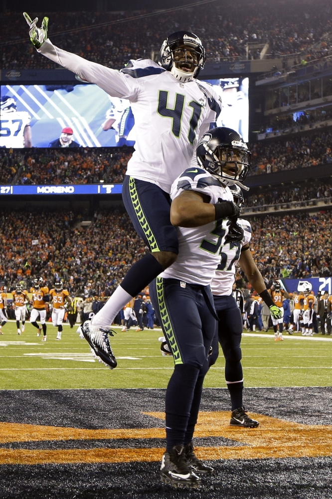 Seattle Seahawks' Byron Maxwell, top, celebrates with teammate Malcolm Smith after Smith scored a touchdown during the first half of the NFL Super Bowl XLVIII football game Sunday, Feb. 2, 2014, in East Rutherford, N.J. (AP Photo/Mark Humphrey)