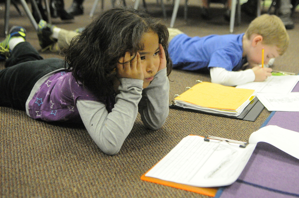 Zion Armstrong, left, thinks about what to write next as classmate Justin Stein works next to her on the floor during a writing workshop last fall in Jessica Gurney's classroom at Manchester Elementary School.