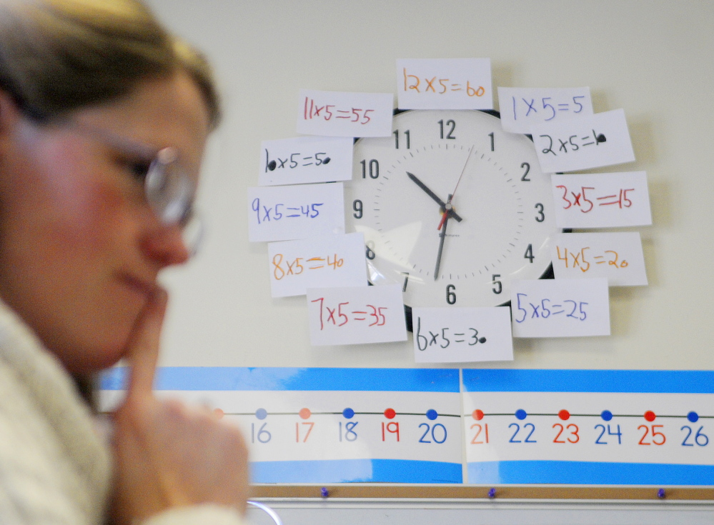 """TALKING NUMBERS: The clock behind Readfield Elementary School third grade teacher Abby Shink is adorned with equations as she listens Wednesday to her class work through an equation with a """"number talk,"""" an instructional activity RSU 38 uses to get students to discuss and critique arguments in math, as required in the Common Core State Standards."""