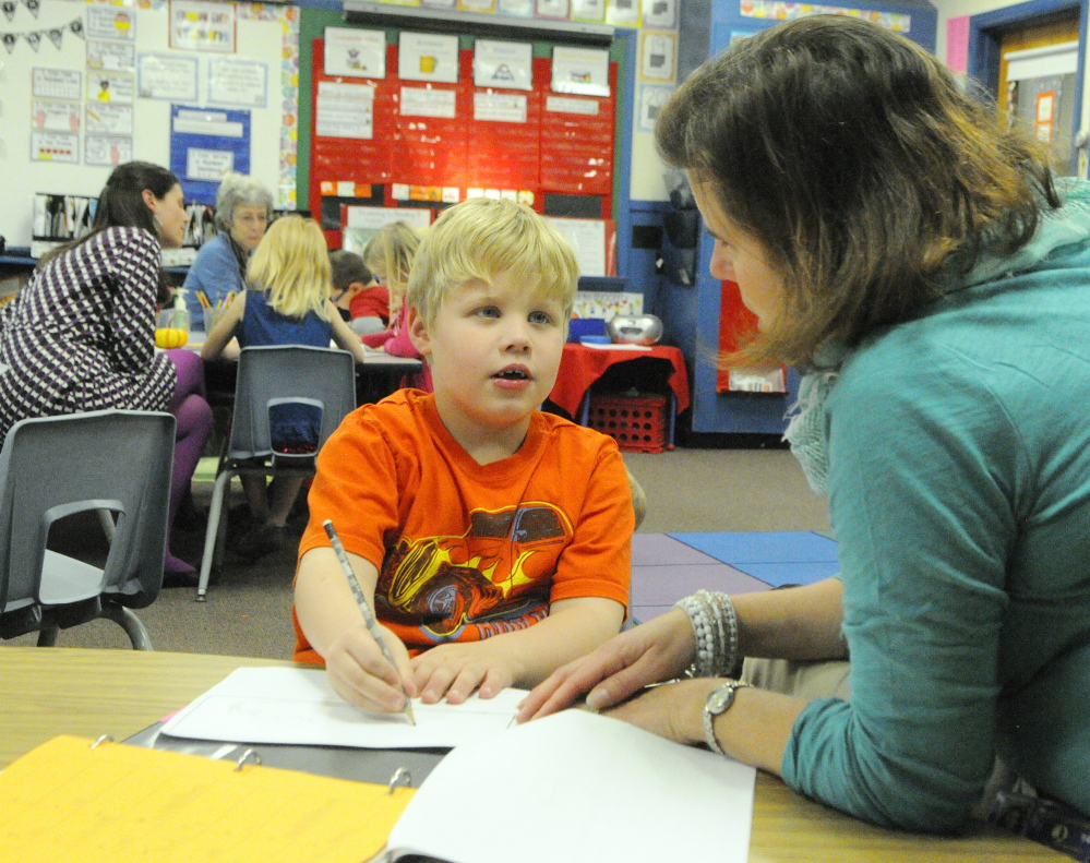 Mason Pare, left, tells Ed Tech Jessica Dwyer about his plans to write about monster trucks during a writing workshop last fall in Jessica Gurney's classroom at Manchester Elementary School.