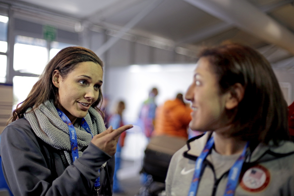 U.S. bobsled brakeman Lolo Jones, left, gestures to teammate, pilot Elana Meyers, during a television interview as the pair arrive at the 2014 Winter Olympics recently in Sochi, Russia.