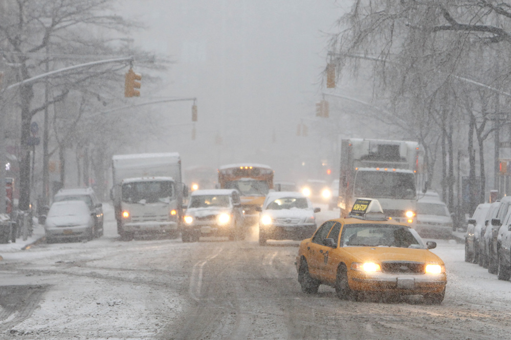 Traffic moves slowly down Hudson Street Monday in New York. After several days of mild weather, snow has returned to the Northeast.