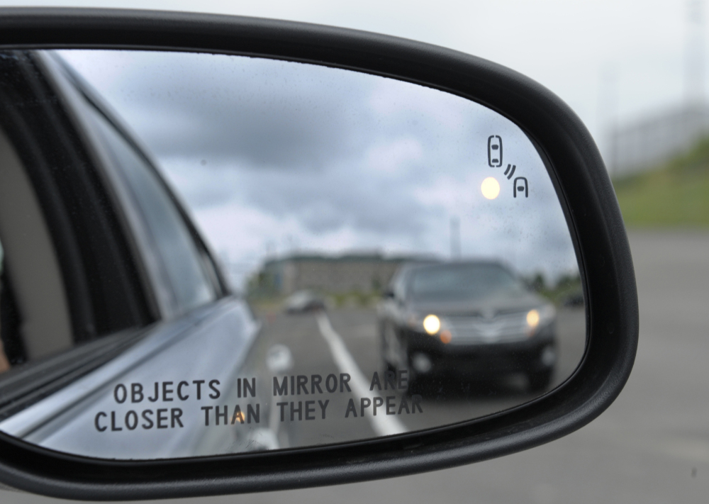A side mirror on a Ford Taurus shows a collision warning signal at an automobile testing area in Oxon Hill, Md. Federal officials announced Monday that they will push to require automakers to equip new cars and light trucks with technology that enables vehicles to communicate with each other.