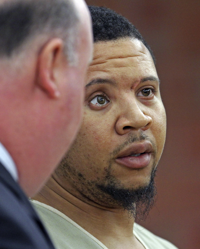 Alexander Bradley listens to his attorney Robert Pickering, left, during arraignment on weapons charges Tuesday in Superior Court in Hartford, Conn. Bradley was shot in the leg outside a Hartford nightclub Sunday night, where police said he returned gunfire.