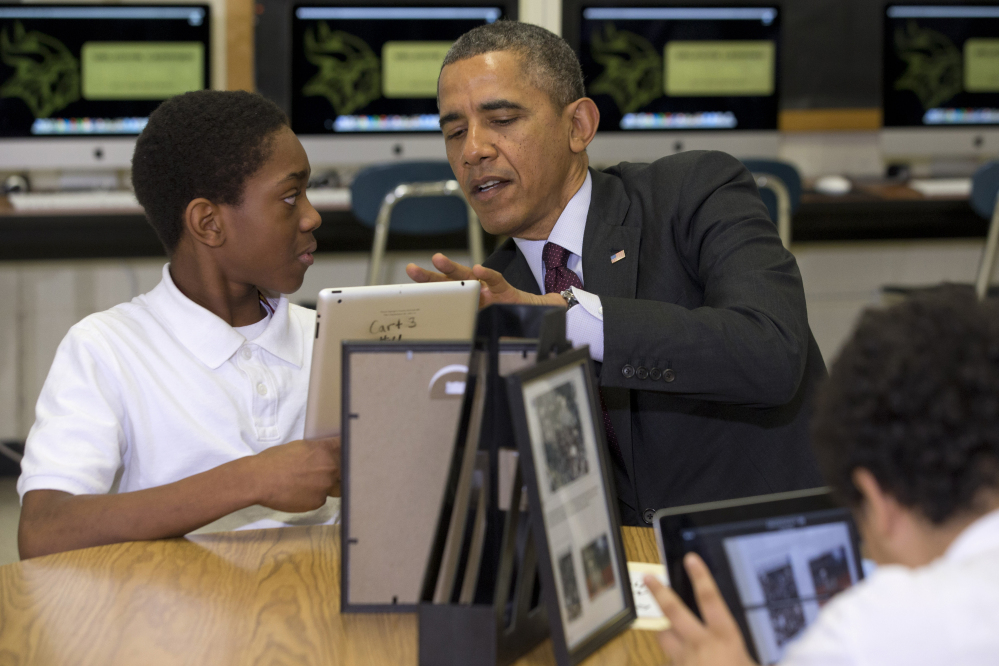President Barack Obama looks at a student's iPad project Tuesday at Buck Lodge Middle School in Adelphi, Md., where he spoke about his goal of connecting 99 percent of students to next-generation broadband and wireless technology within five years.