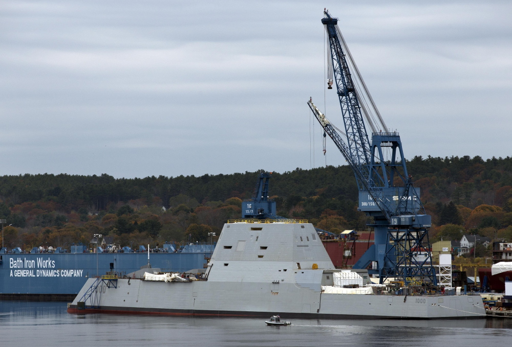 A security boat is dwarfed by the Navy's stealthy Zumwalt destroyer at Bath Iron Works in Bath, in this Oct. 31, 2013, photo. It is like no other U.S. warship, with an angular profile and clean carbon fiber superstructure that hides antennas and radar masts.