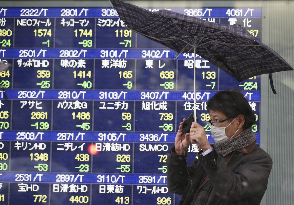 A man reacts to a gust of wind as it starts to snow in front of an electronic stock board at a securities firm in Tokyo Tuesday. Japan's Nikkei 225 stock average dived more than 4 percent Tuesday as weakness in U.S. and Chinese manufacturing sent Asian markets sharply lower. The Nikkei tumbled 4.2 percent to 14,008.47 and is down 14 percent over the past month.