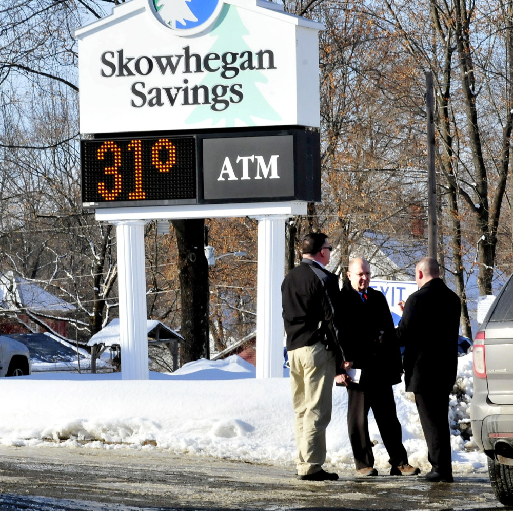 ROBBERY: Police, including Somerset County Chief Deputy Dale Lancaster, center, consult outside the Skowhegan Savings bank branch in Bingham after it was robbed Tuesday.