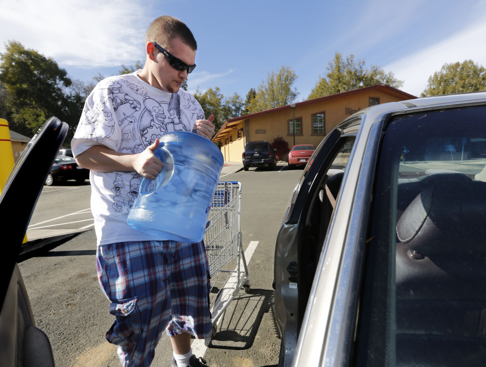 Forrest Clark loads five-gallon bottles of water, purchased at a local store, into his car in Willits, Calif. Clark, who said he doesn't like the taste of the local water, buys 10-15 gallons of bottled water a week to help boost the family water supply.