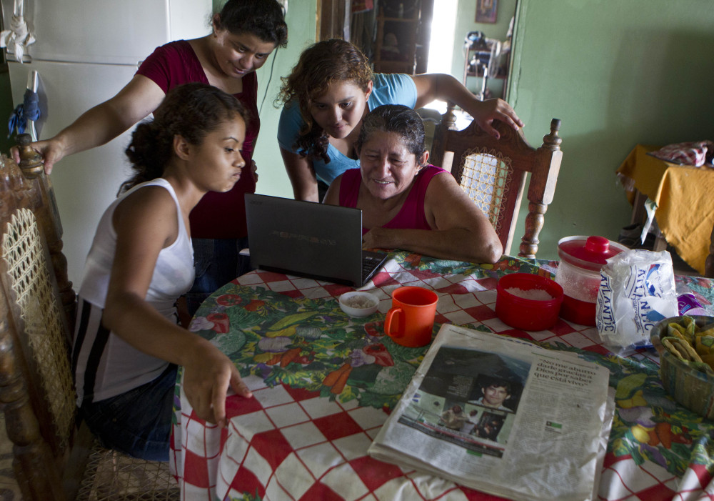 The mother of sea survivor Jose Salvador Alvarenga, Maria Alvarenga, right, his daughter Fatima Alvarenga, second right, and other family members gather at the kitchen table to video chat with relatives living in Maryland, in Garita Palmera, El Salvador on Tuesday. The account of Alvarenga's survival after more than 13 months in an open boat has proven a double miracle for his family, who lost touch with him years ago and thought he was dead.