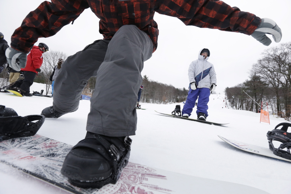 Snowboarders traverse a slope as they make their way toward a chairlift at Blue Hills Ski Area in Canton, Mass., last December. Massachusetts ski areas are among those threatened by warming winters.