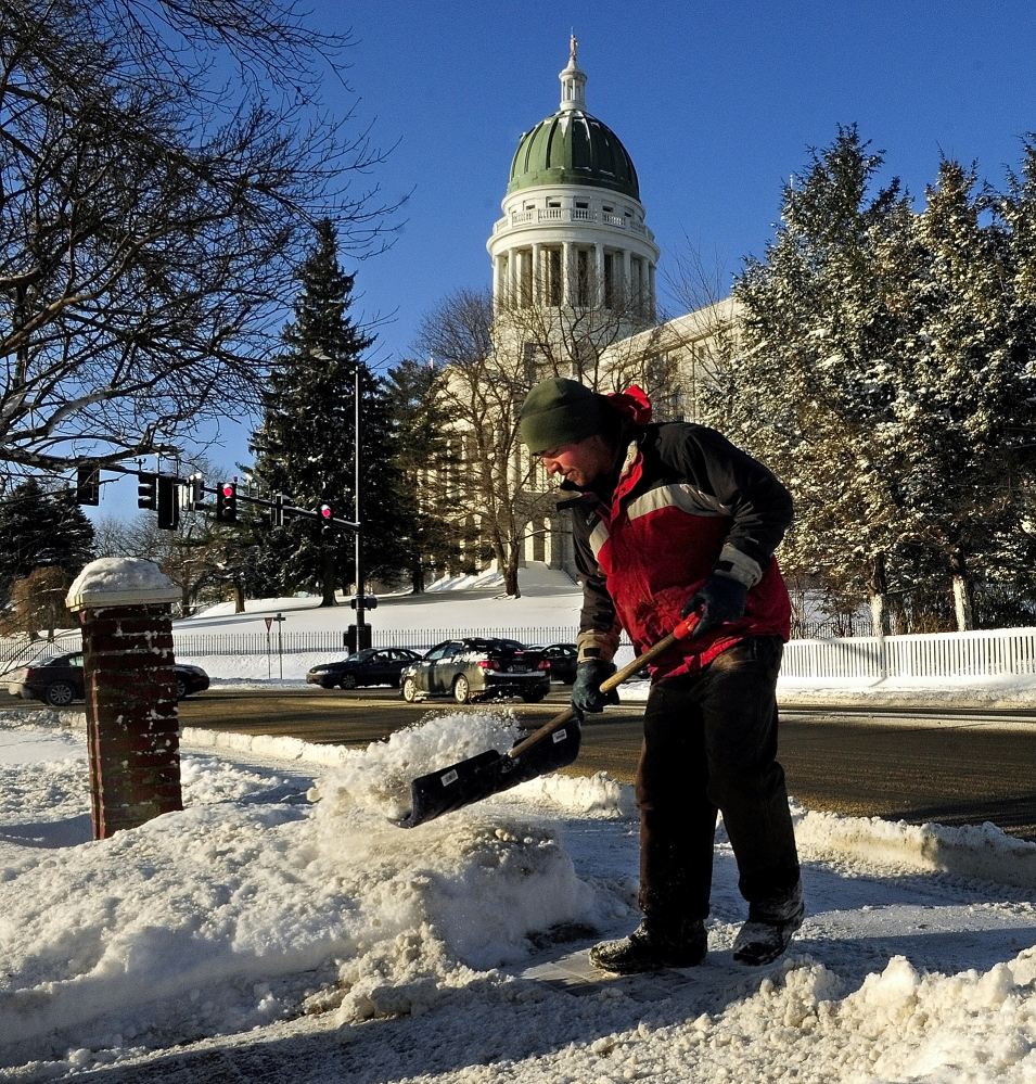 Josh Nolls shovels snow in front of a state office building across from the State House on Thursday. Nolls and other Bureau of General Services employees had been working since early in the morning to get the capitol complex and other state offices ready for business the day after the government shut down early because of Wednesday's snow storm that dropped about 9 inches in Augusta.