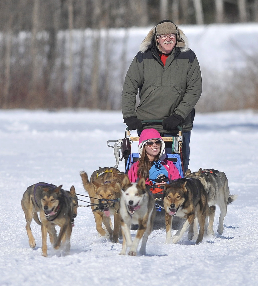 Dog Sleding: David Farr, a musher with Heywood Kennel Sled Dog Adventures in Augusta, drives a team of dogs with Elaine George and her son Alexander, 2, on board during the annual Winter Carnival at Quarry Road Recreational Area in Waterville on Saturday.