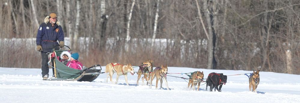 Mush: Kevin Quist, a musher with Heywood Kennels Dog Sled Adventures in Augusta, drives a team of dogs with Jackie Bean, 11, back, and Zoie Ouellette, 5, front, on board during Winter Carnival at Quarry Road Recreational Area in Waterville on Saturday.