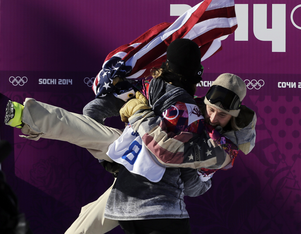 United States' Sage Kotsenburg, right, is carried by Norway's Staale Sandbech after Kotsenburg won the men's snowboard slopestyle final at the Rosa Khutor Extreme Park, at the 2014 Winter Olympics, Saturday.