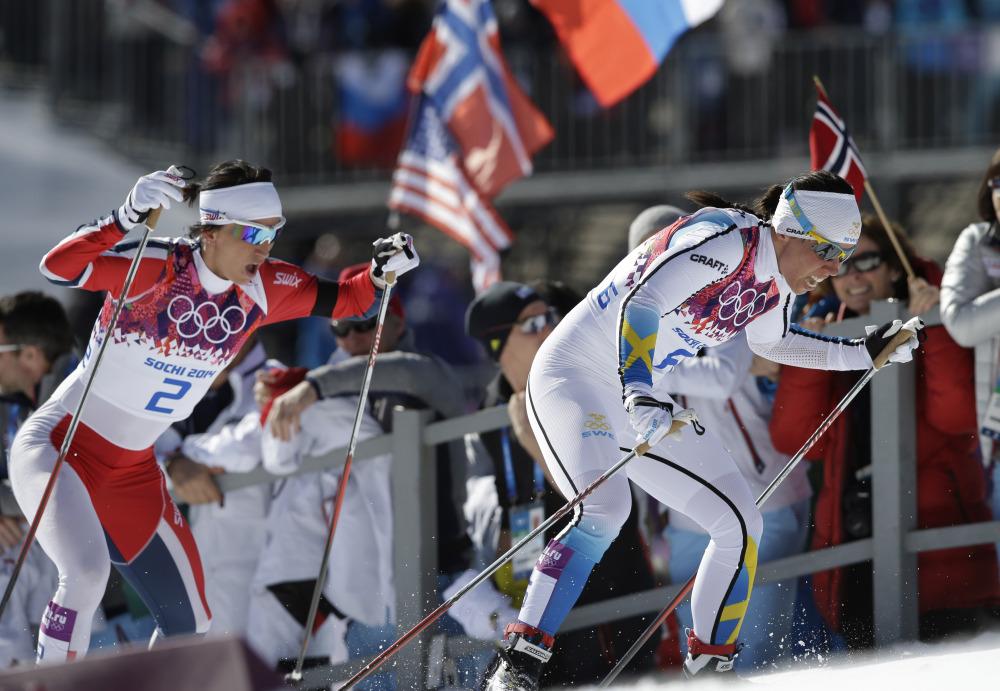 Norway's gold medal winner Marit Bjoergen, left, and Sweden's silver medal winner Charlotte Kalla climb a hill during the women's cross-country 15k skiathlon Saturday.