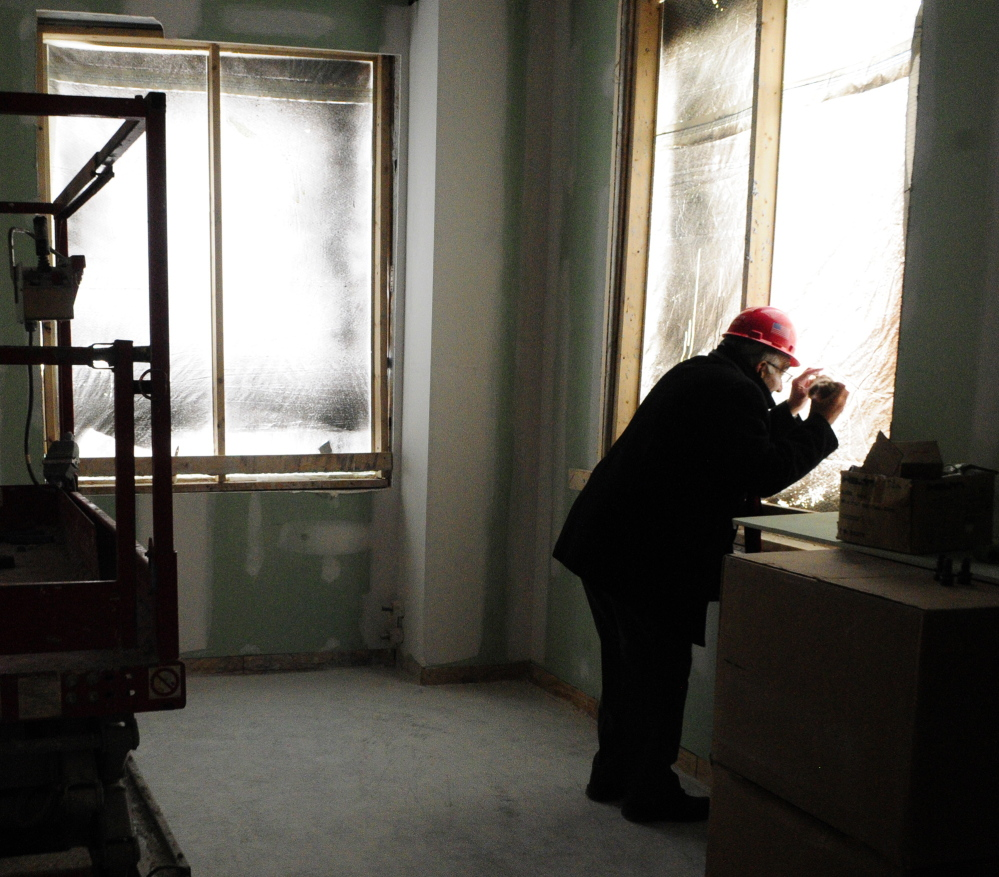 Courthouse progress: Maine Supreme Judicial Court Associate Justice Joseph Jabar looks through a hole in plastic window covering on Thursday during a tour of the new court building in Augusta to check out the view of the State House from the window of what will be his office.
