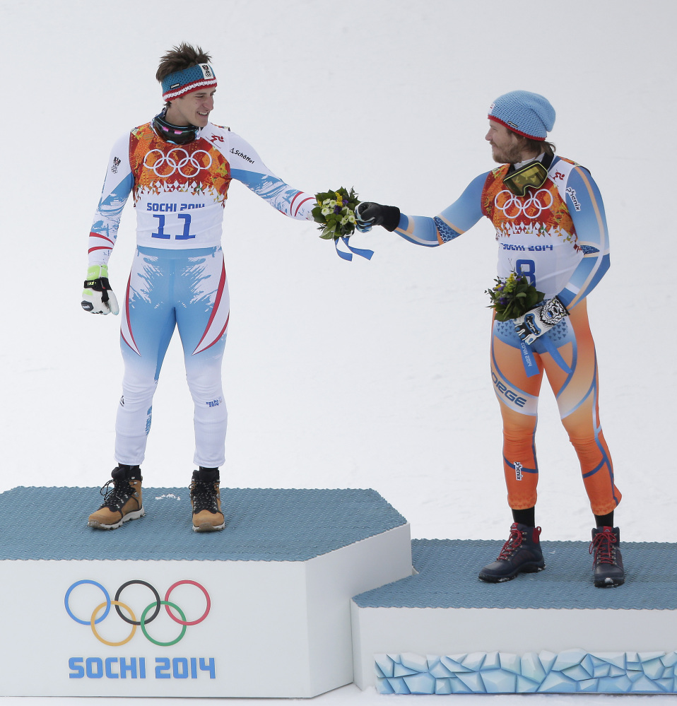 Austria's Matthias Mayer, left, and Italy's Christof Innerhofer celebrate during the flower ceremony after finishing the men's downhill event at the 2014 Winter Olympics on Sunday in Krasnaya Polyana, Russia.