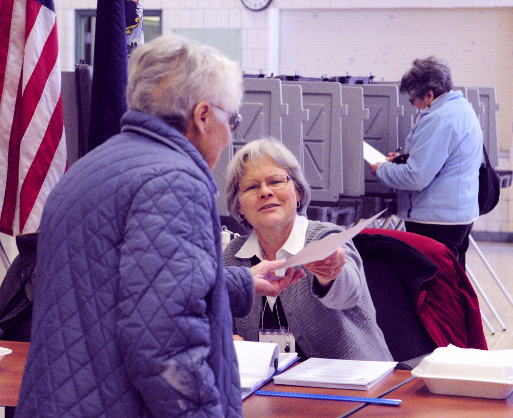 BUDGET FINALIZED: Election worker Jan Tewksbury, center, hands a ballot to a voter Tuesday during a vote on the school budget at the Winthrop Town Office.