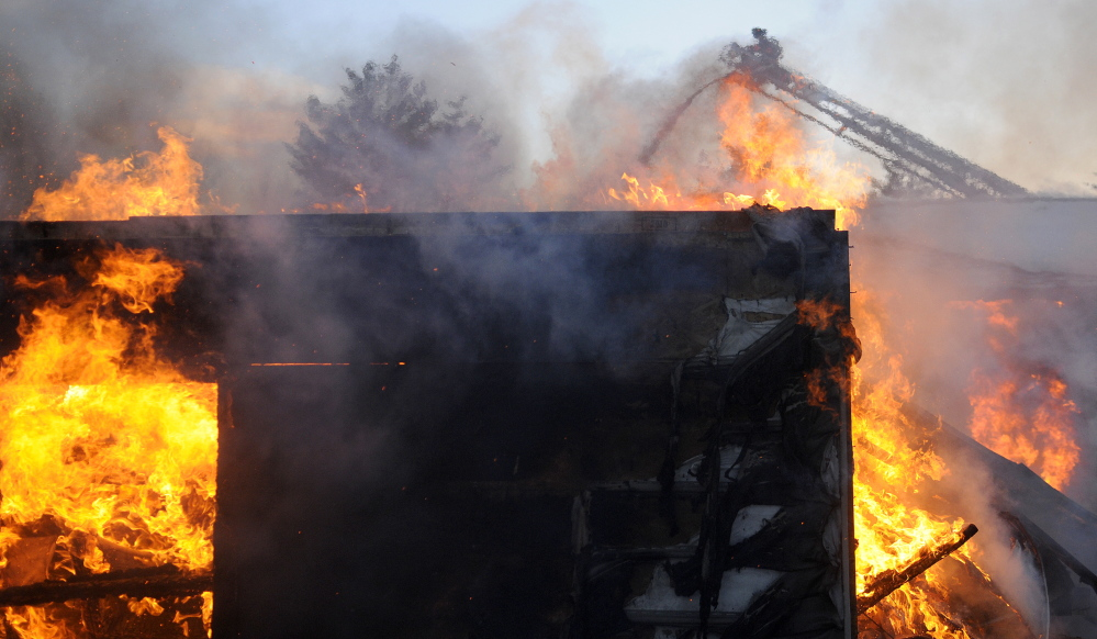 BURNED: A firefighter sprays water Tuesday from the aerial on a ladder truck at a blaze that damaged a new home Tuesday in Farmingdale. Several fire companies from surrounding towns responded to the blaze at the large home off the Hallowell-Litchfield Road.